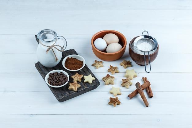 Jarra de leche, cuencos de granos de café y harina en una tabla de madera con galletas de estrella, canela, huevos, colador de harina vista de ángulo alto sobre un fondo de tablero de madera blanca