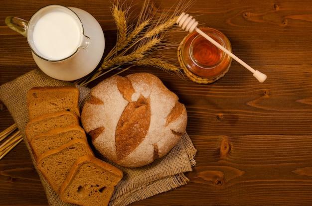 Jarra de leche, pan de centeno y un tarro de miel.