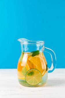Jarra con limonada casera con fondo azul.