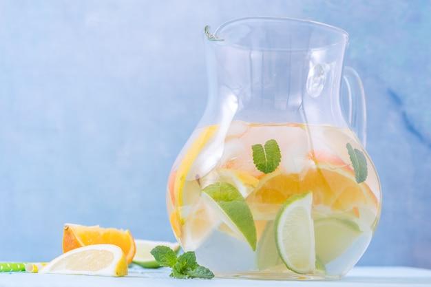 Jarra de limonada con rodajas de limón, naranja y lima