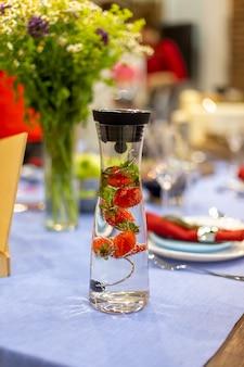 Una jarra llena de agua y fresas se encuentra en una mesa azul servida. de cerca, enfoque suave. la mesa servida está en el fondo desenfocado.