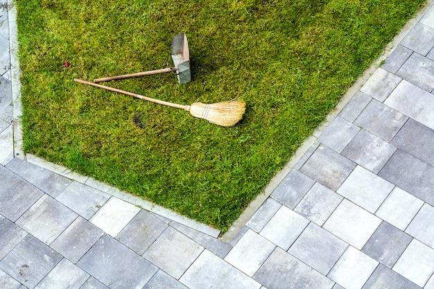 Jarra recogedor y una escoba en un césped de hierba verde. herramientas de jardinería.