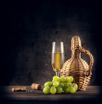 Jarra trenzada y una copa de vino blanco