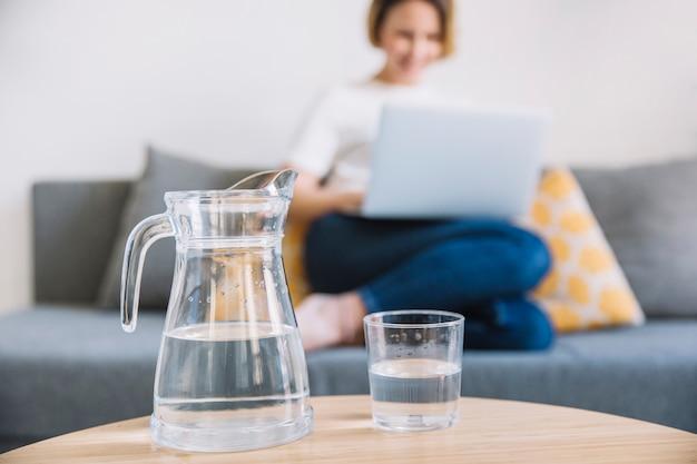 Jarra y vaso de agua cerca de la mujer