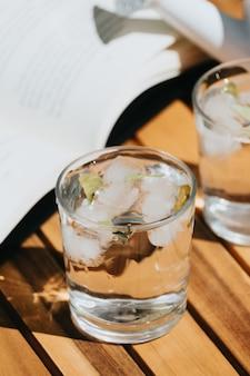 Jarra y vaso de agua sobre una mesa de madera durante un día soleado de verano