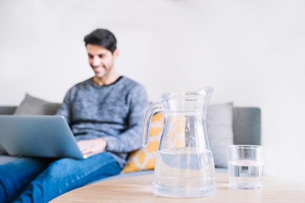 Jarra y vaso cerca del hombre con la computadora portátil