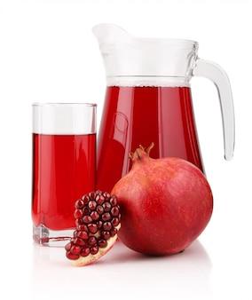 Jarra y vaso de jugo de granada con frutas aisladas