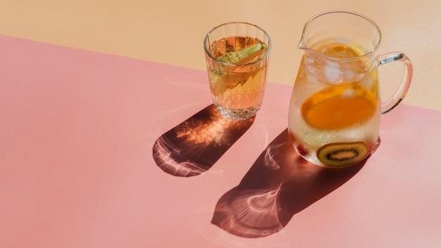 Jarra y vaso transparente lleno de agua y rodajas de frutas.