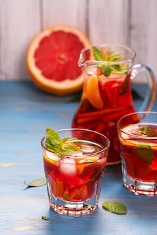 Jarra y vasos con limonada casera de cítricos.