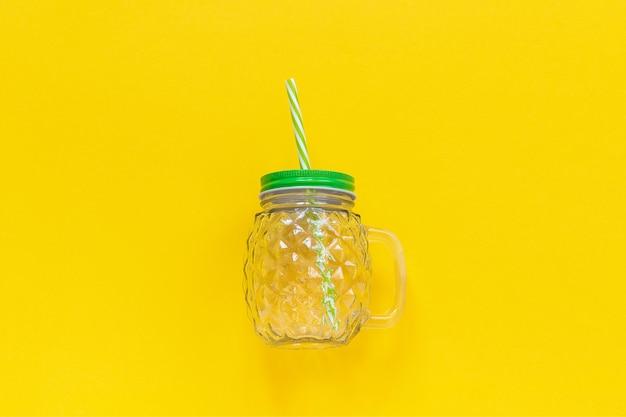 Jarra de vidrio vacía en forma de piña con tapa verde y paja para bebidas de frutas o vegetales