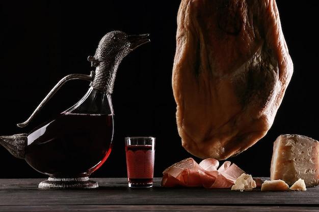 Una jarra de vino en forma de pato, una copa de vino, una pierna de jamón de parma y queso. fondo negro.