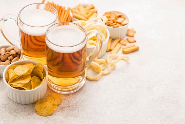 Jarras de cerveza de alto ángulo y sabrosos bocadillos