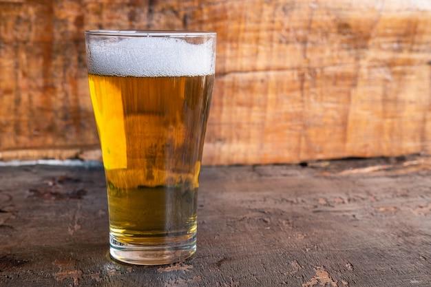 Jarras de cerveza y botellas de cerveza en una mesa de madera