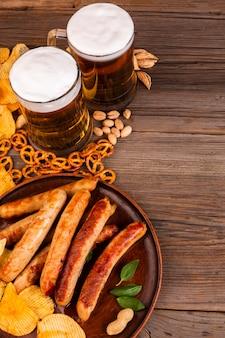 Jarras de cerveza y plato con salchichas