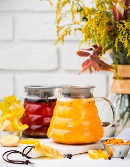 Jarras de vidrio con té rojo y té de grosella espinosa