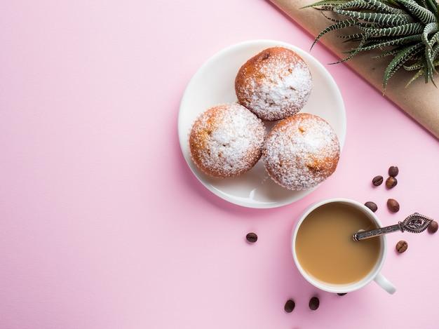 Jarro de leche del café de los molletes del desayuno en un fondo rosado. vista superior flat lay.