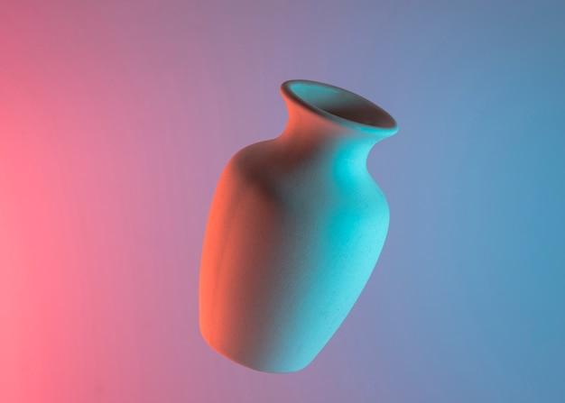 Jarrón de cerámica liso blanco en el aire contra el fondo de color azul y rosa