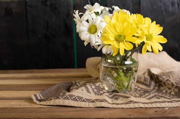 Un jarrón de cristal de flores amarillas y blancas.