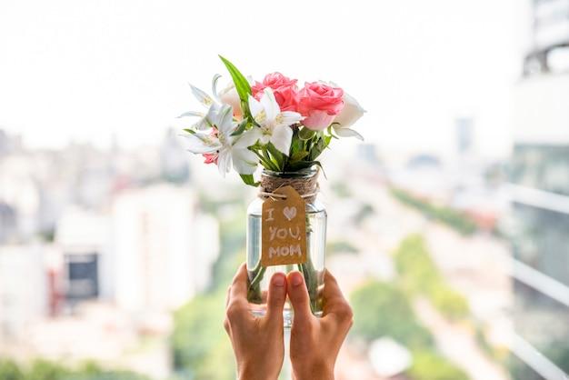Jarrón de flores para el día de la madre en manos.