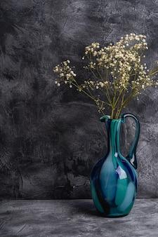 Jarrón jarra azul con flores blancas secas de gypsophila a granel en la pared de piedra con textura oscura, ángulo de visión