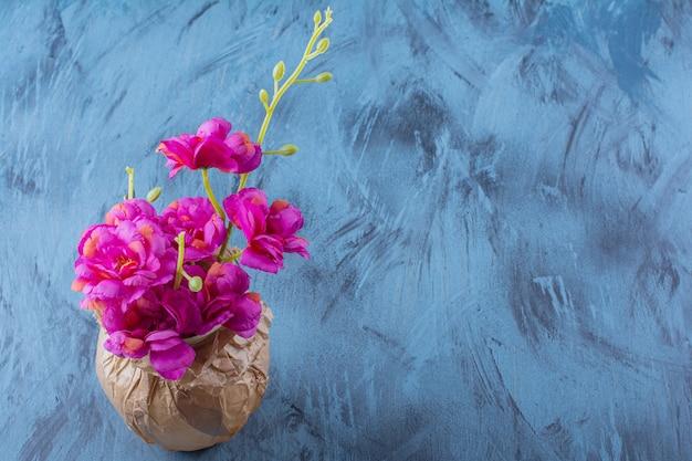 Un jarrón de papel con hermosas flores frescas de color púrpura sobre azul.