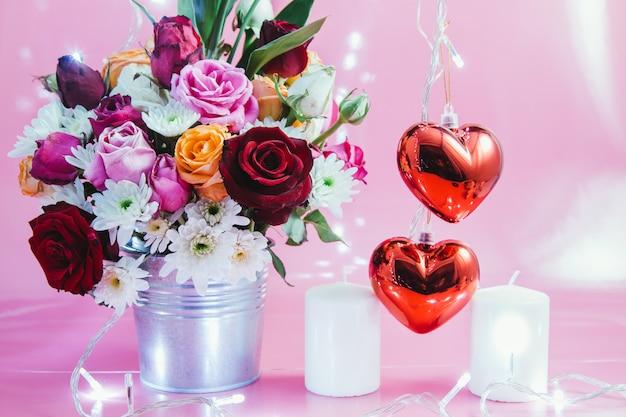 Jarrón con ramo de rosas, corazón rojo y vela blanca.