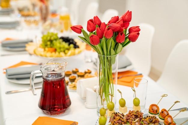 Jarrón con un ramo de tulipanes rojos en la mesa festiva. sirviendo la mesa con aperitivos, canapés, ensaladas en frascos. abastecimiento. negocio de los restaurantes.