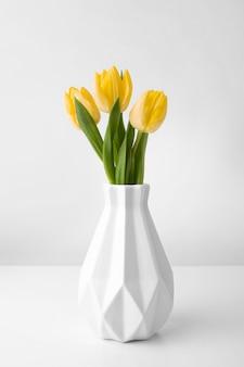 Jarrón con tulipanes en mesa