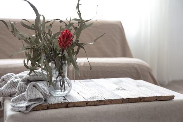 Jarrón de vidrio con flor de protea en el interior de la habitación, copie el espacio.