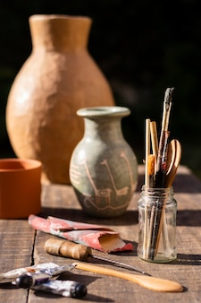 Jarrón de vista frontal y herramientas de pintura