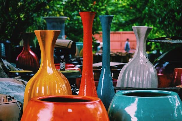Los jarrones de cerámica hechos a mano (tarro) de colores (rojo, azul, gris y amarillo) para el fondo de arte