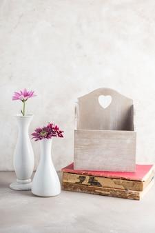 Jarrones de flores y caja de tarjeta postal en libros colocados en mesa