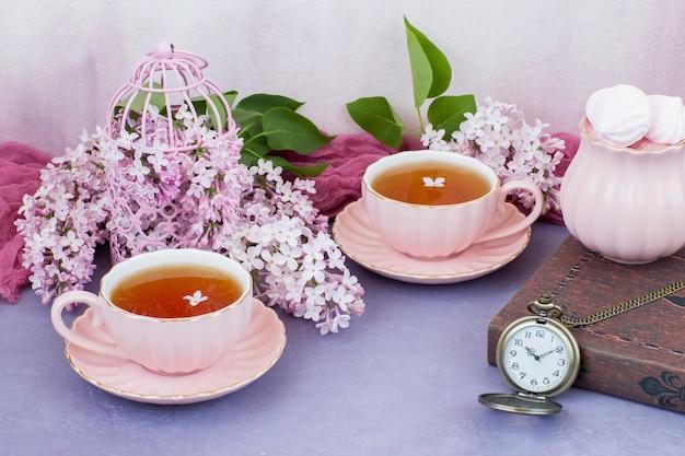 En una jaula decorativa rosa, rosa lila, dos tazas de té, un libro y un reloj de bolsillo.