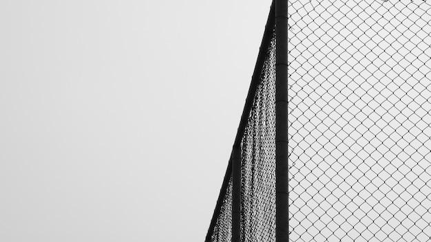 Jaula de red de metal en el fondo monocromo de la cárcel