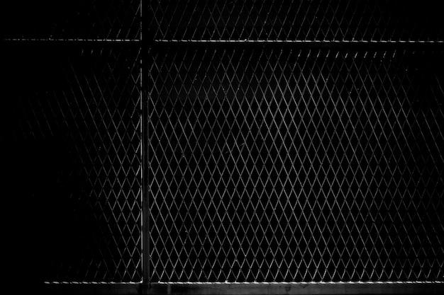 Jaula de red de metal en la oscuridad.