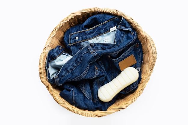 Jeans en canasta de lavandería sobre superficie blanca. vista superior