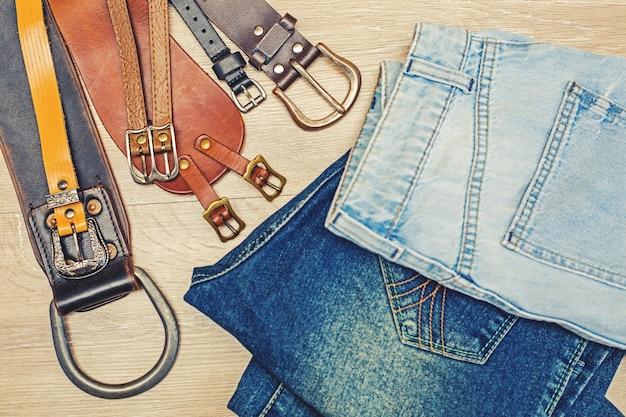 Jeans elegantes con cinturones en la pared de madera