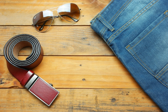 Jeans, gafas de sol y cinturón de cuero en la cosecha de madera con espacio de copia