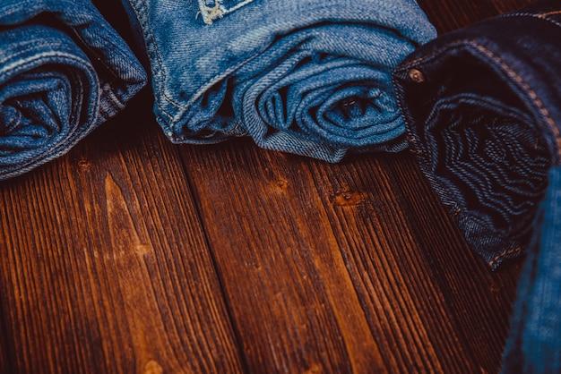 Jeans roll frayed o jeans azul colección denim sobre madera