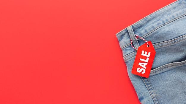 Jeans de vista superior con etiqueta de venta sobre fondo rojo