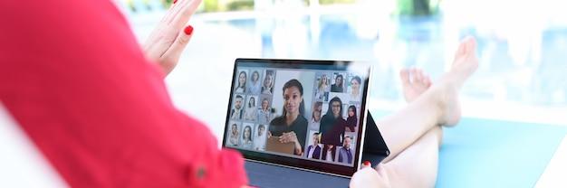 La jefa está llevando a cabo una reunión en línea en una tableta mientras está acostada en una tumbona junto a la piscina