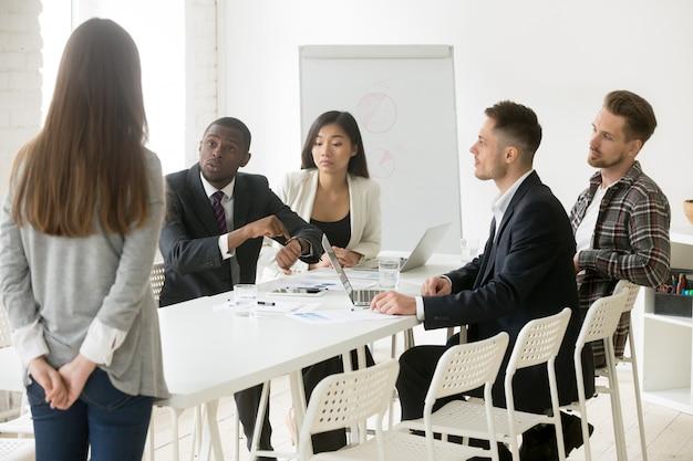 Jefe africano enojado regañando a un empleado por llegar tarde a la reunión