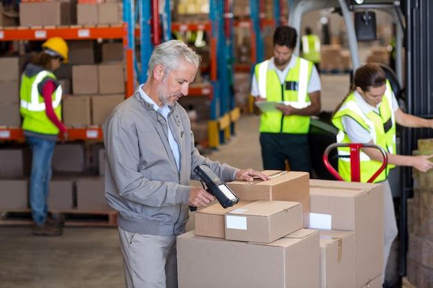 Jefe de almacén escaneando las cajas