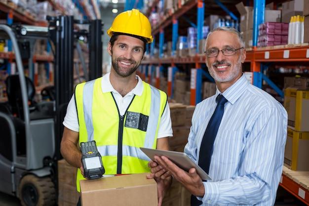 Jefe de almacén con tableta digital mientras el trabajador de sexo masculino escanea el código de barras