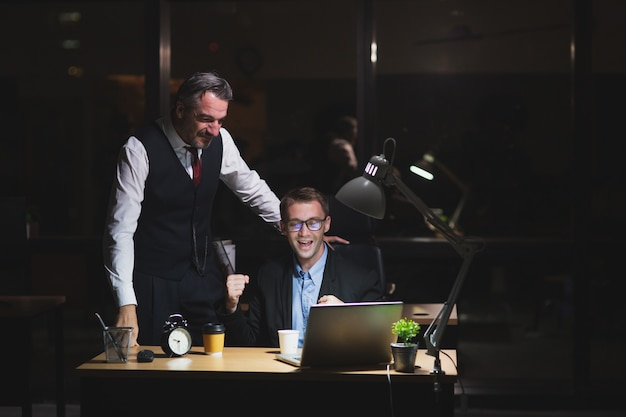 Jefe caucásico trabajando tarde stand con colega en el cargo por la noche. hombre de negocios mira portátil con compañero de trabajo feliz de éxito con el trabajo. trabajo nocturno y concepto de horas extra