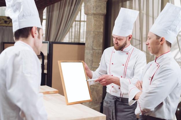 Jefe de cocina y su personal en la cocina. interactuando en cocina comercial.