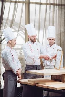 Jefe de cocina y su personal en la cocina interactuando con comerciales.