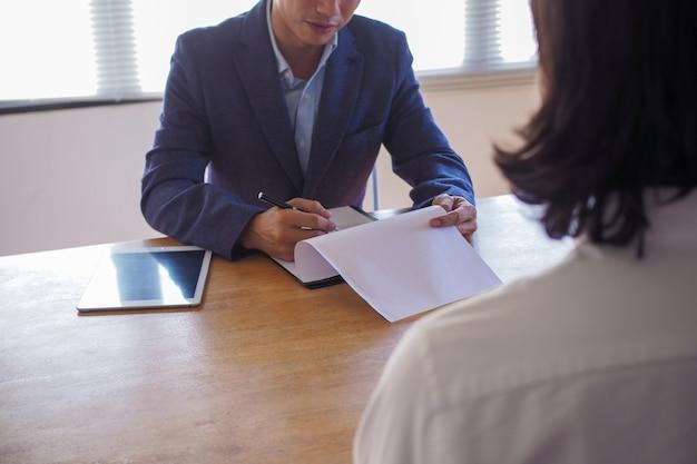 Jefe ejecutivo entrevistando a candidato y sosteniendo una tableta