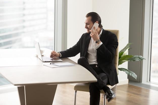 Jefe de empresa en contacto con socios por teléfono.