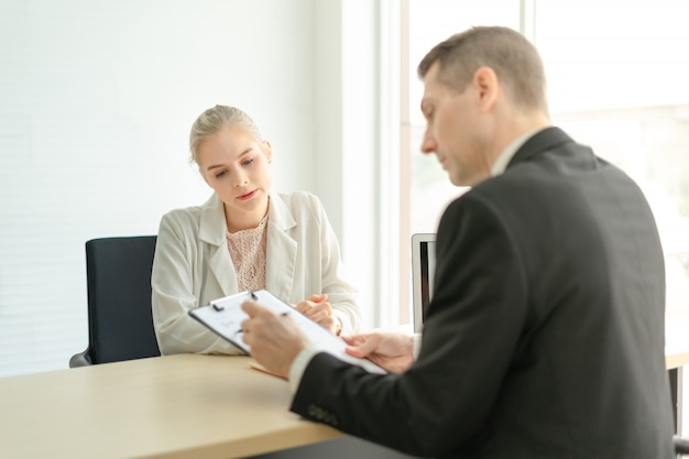 Jefe empresario hablando de informe con feliz empleada en el escritorio en la oficina